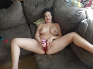 ehefrau befriedigt sich mit einem vibrator auf der couch und geniesst es fotografiert zu werden