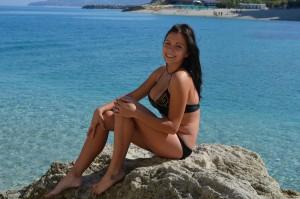 geile milf mit dicken titten im bikini posiert auf einem kleinen felsen auf privatem urlaubsfoto