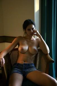 auf einem stuhl sitzend oben ohne in jeans hot pants